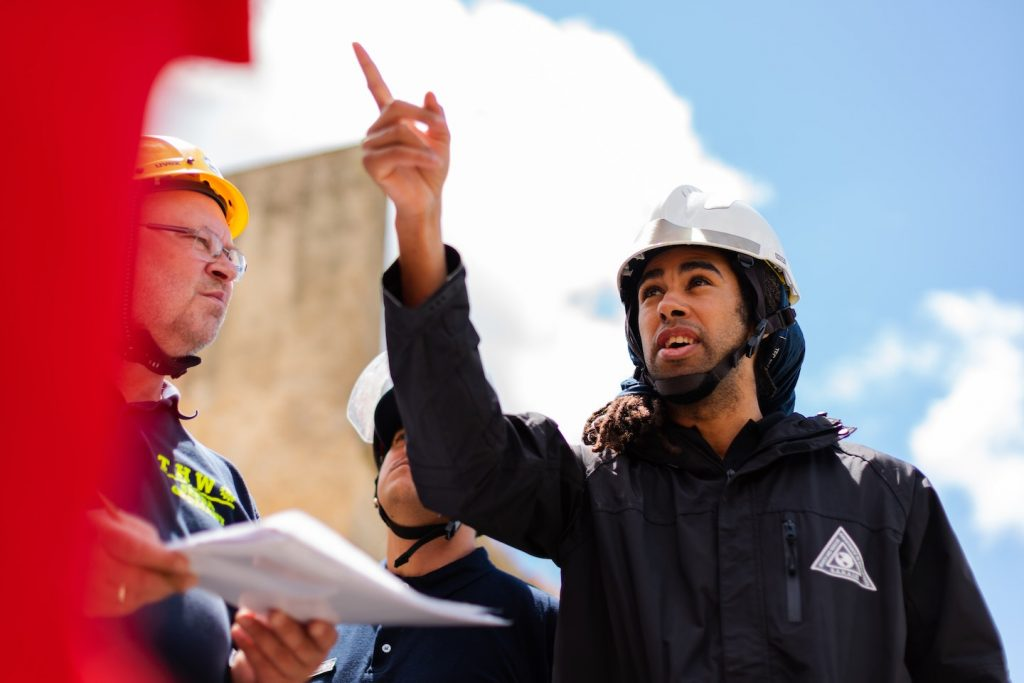 engineer wearing hardhat and pointing