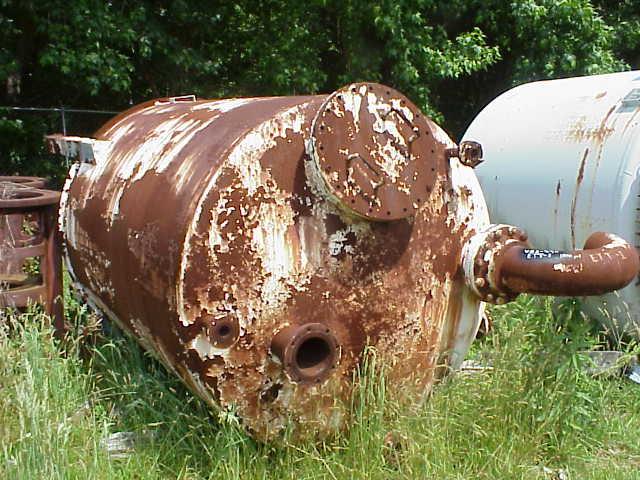 rusted pressure vessel in a field