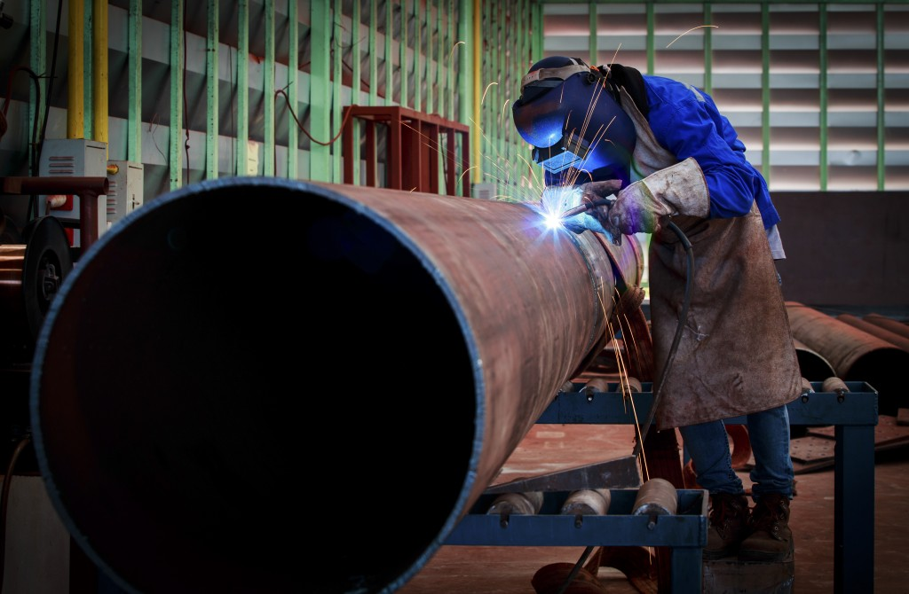 A pipe fabricator working in a fabrication shop with overhead cranes and hoists, a variety of hand tools, grinders and cutting equipment.